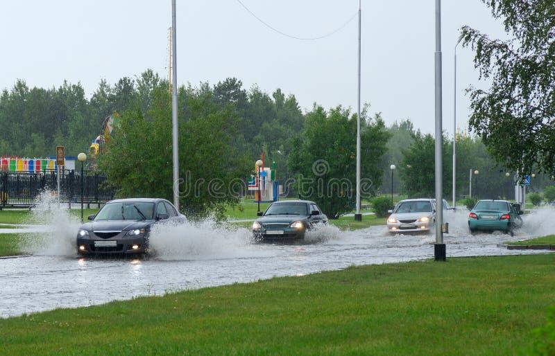 Auto's op een overstroomde straat in de stad stock afbeeldingen