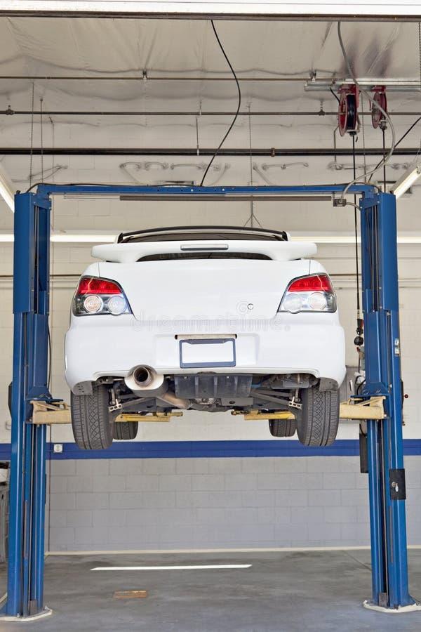 Auto's op hijstoestel bij reparatiewerkplaats stock afbeeldingen
