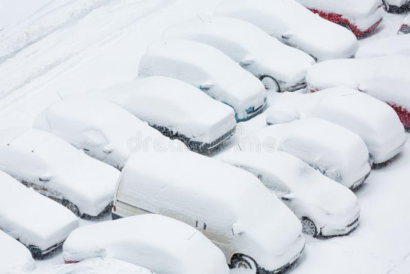 Auto's in sneeuw op een parkeerterrein worden behandeld dat royalty-vrije stock foto's