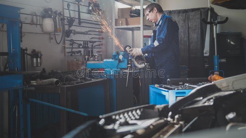 Auto seminarium för bil - den manliga caucasian mekanikerarbetaren arbetar med cirkelsågen arkivfoton