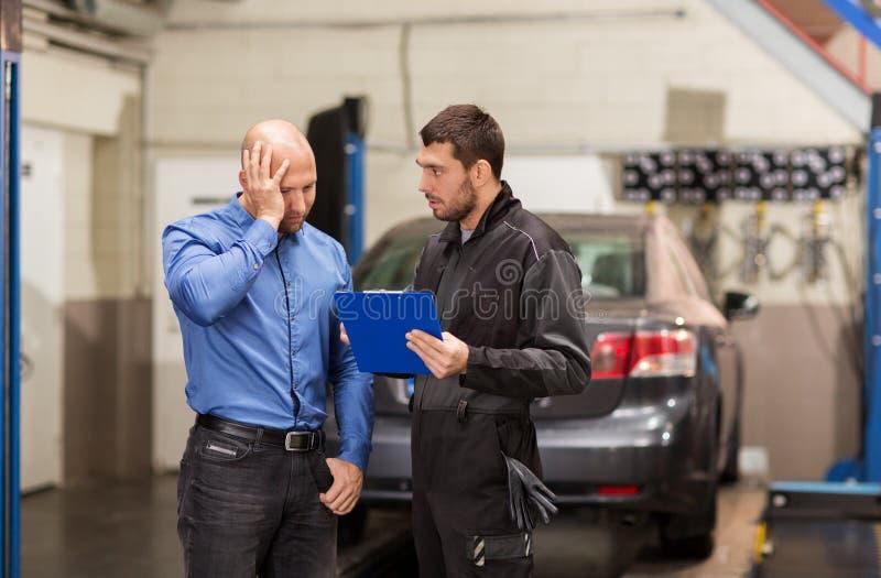 Auto mechanic and customer at car shop royalty free stock photo