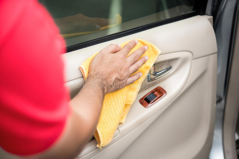 Auto service staff cleaning car door interior panel with microfiber cloth. Car detailing and valeting concept stock photo
