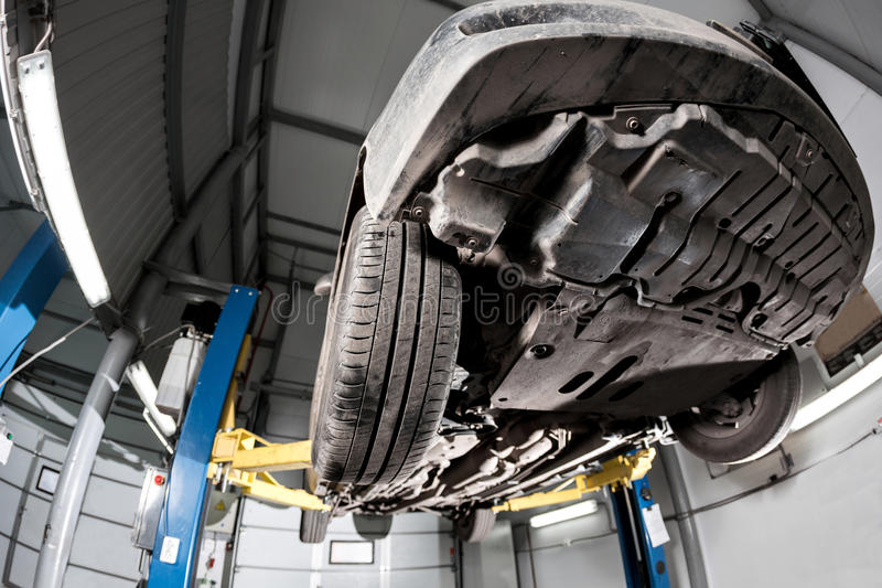 Auto sikt från botten Främre bilupphängning garagemekanikern lyftte bilen på elevatorn royaltyfria bilder