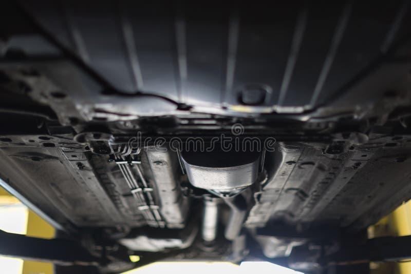 Auto sikt från botten Garagemekanikern lyftte bilen på elevatorn royaltyfria foton