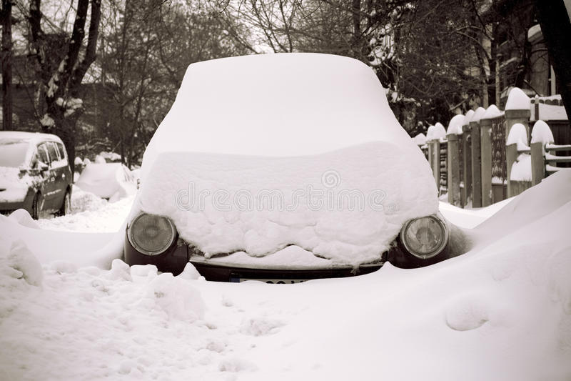 Auto in sneeuw op een straat met slechts koplampen het tonen wordt geplakt die stock fotografie