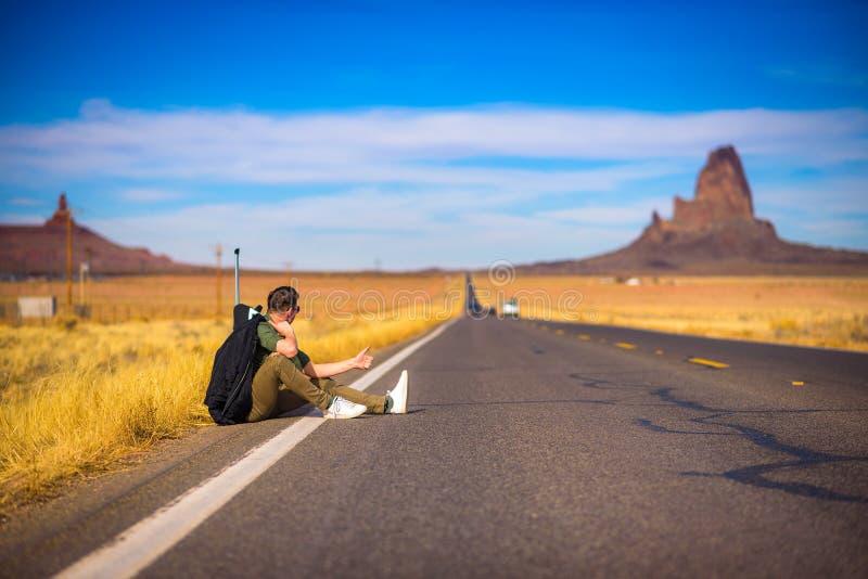 Auto-stoppeur fatigué avec la valise se reposant sur une route image libre de droits