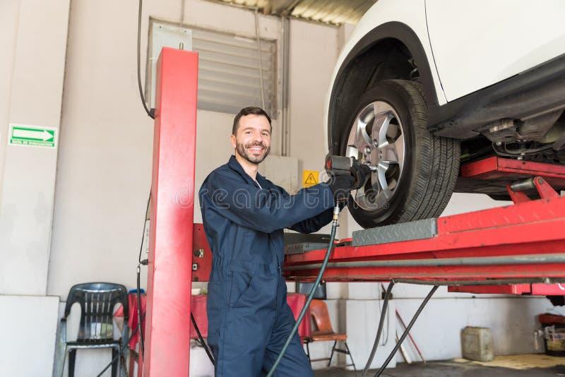 Auto tekniker Fixing Tire Nuts med den elektriska skruvnyckeln i garage arkivbilder