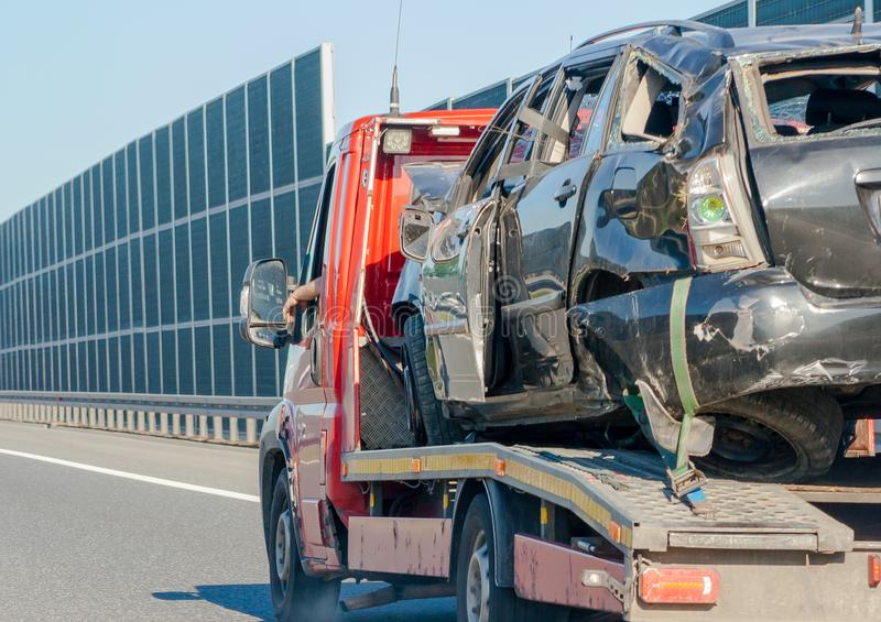 Auto after the tow truck accident. A completely destroyed car transported by a tow truck. stock photography