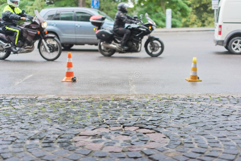Auto traffic on stone road in old town, motorcycles, cars driving along road. Copy space, place for text stock photo