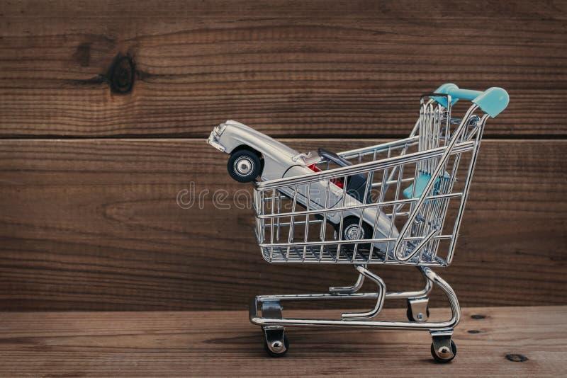 Auto und Einkaufswagen auf Holz lizenzfreie stockbilder
