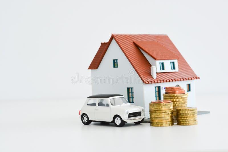Auto und Haus modellieren mit Stapel Münzen, die auf weißem Hintergrund lokalisiert werden lizenzfreie stockfotos