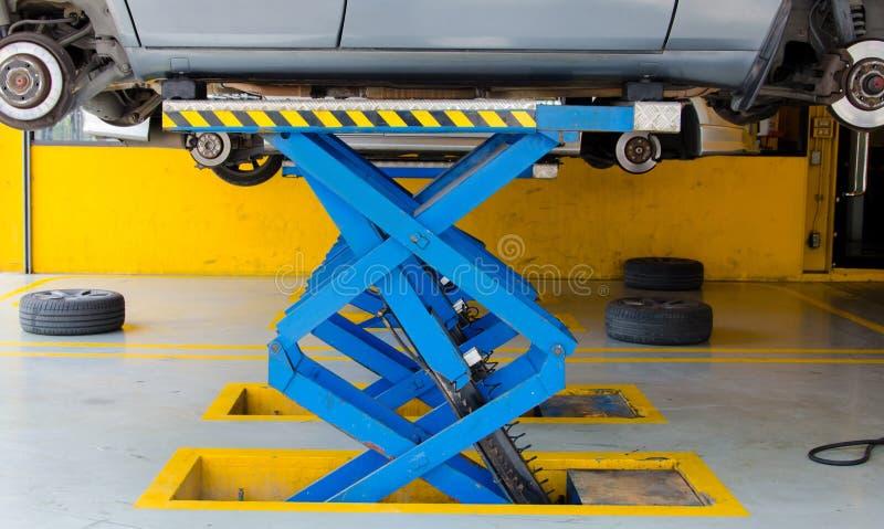 Auto unter Reparatur auf Hebemaschine an der Tankstelle lizenzfreie stockbilder