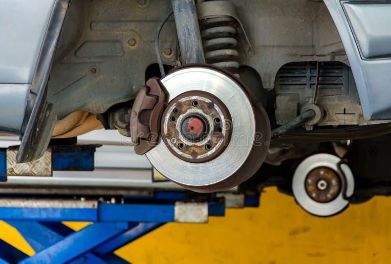 Auto unter Reparatur auf Hebemaschine an der Tankstelle lizenzfreie stockfotos