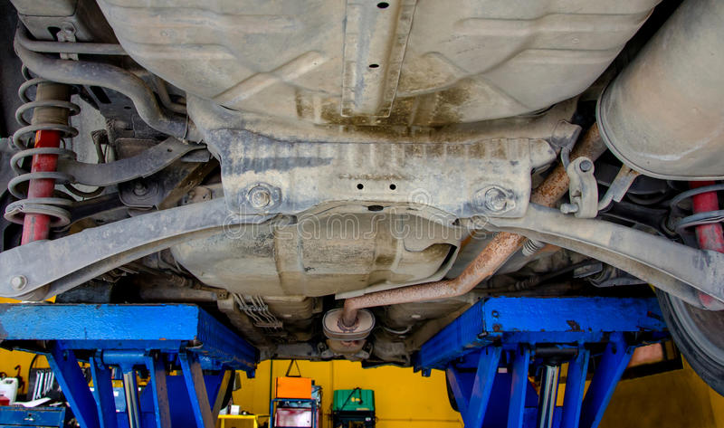 Auto unter Reparatur auf Hebemaschine an der Tankstelle stockbilder