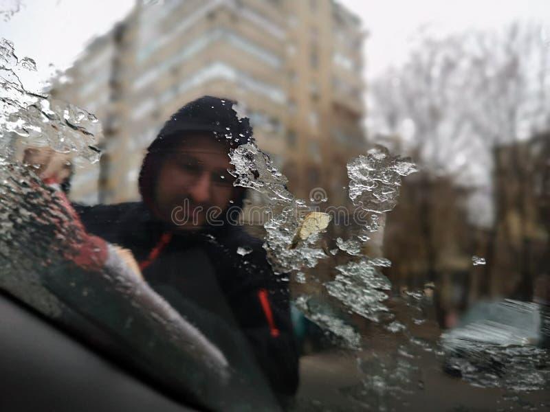 Auto van het mensen de schoonmakende autoraam van vorst in de wintertijd stock foto