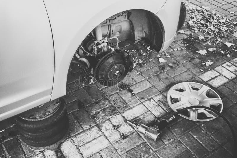 Auto zonder wiel bij de dienst De vervangingsconcept van de autoband stock foto's