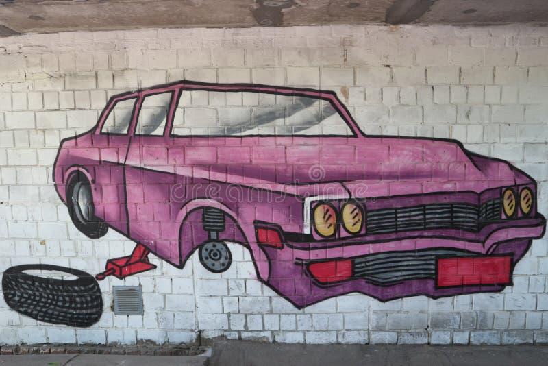 Auto zonder wiel in de reparatie: graffiti op de muur stock fotografie