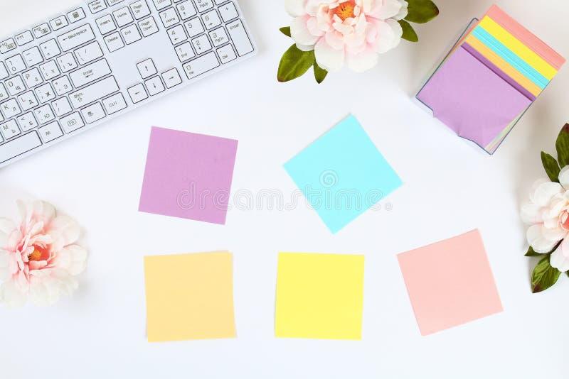 Autoadesivi appiccicosi multicolori della nota su un desktop bianco accanto ad una tazza da caffè e ad una tastiera Vista superio fotografia stock