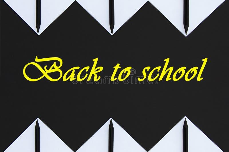Autoadesivi bianchi con le matite nere allineate con un modello geometrico su un fondo nero Testo scritto di nuovo a scuola immagine stock libera da diritti