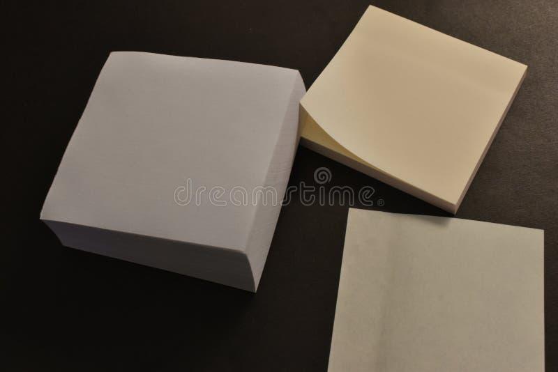 Autoadesivi di carta dell'ufficio su fondo nero immagine stock