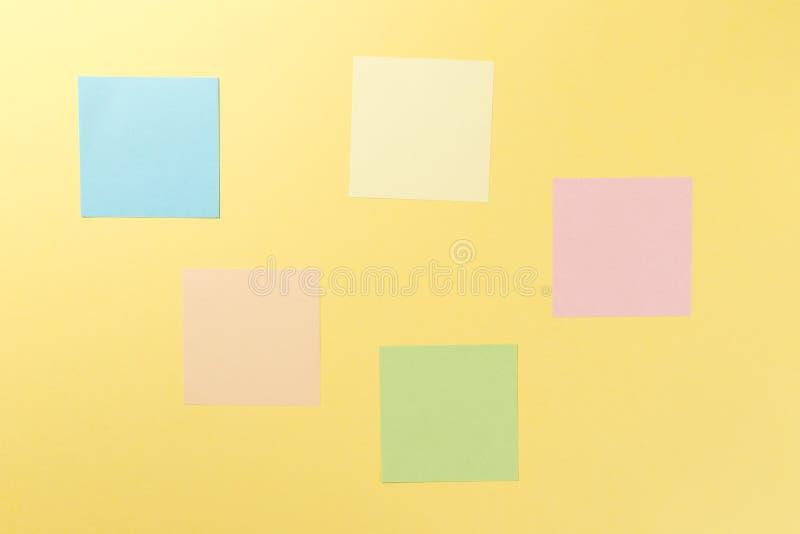 Autoadesivi di carta variopinti su fondo giallo fotografia stock