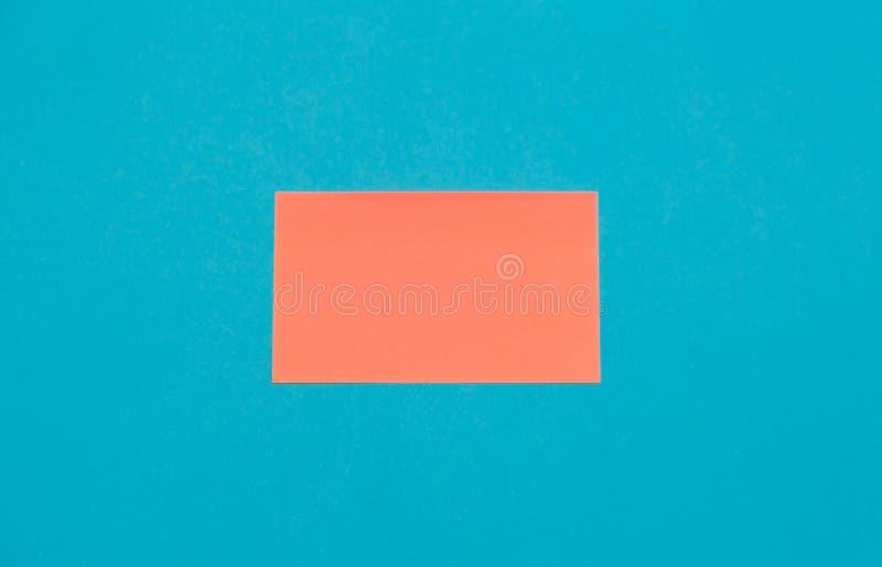 Autoadesivi vuoti rosa del quadrato della carta su fondo blu, spazio della copia fotografia stock