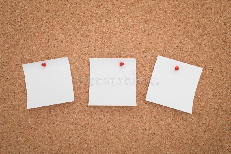 Autoadesivo bianco tre appuntato su un bordo del sughero fotografia stock