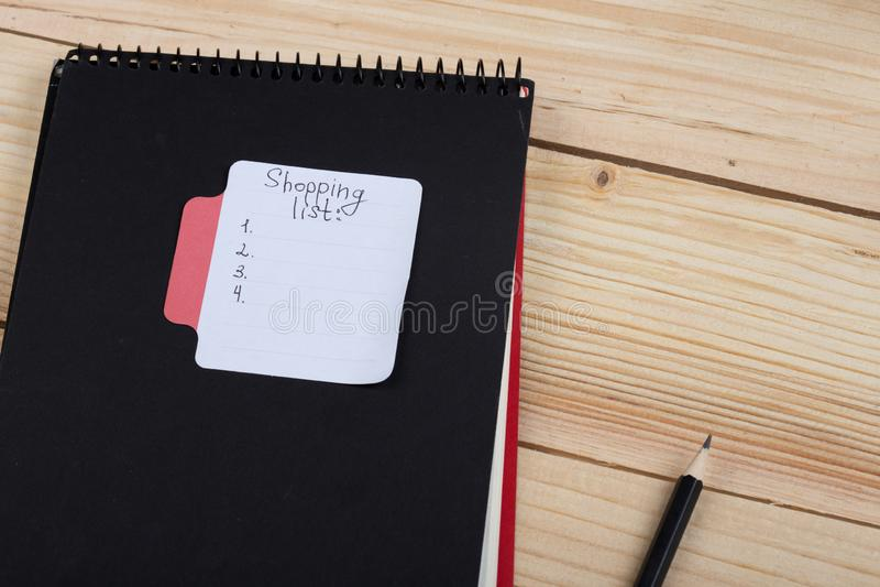 Autoadesivo con la lista di acquisto scritta a mano del testo, il blocco note nero e la matita immagine stock