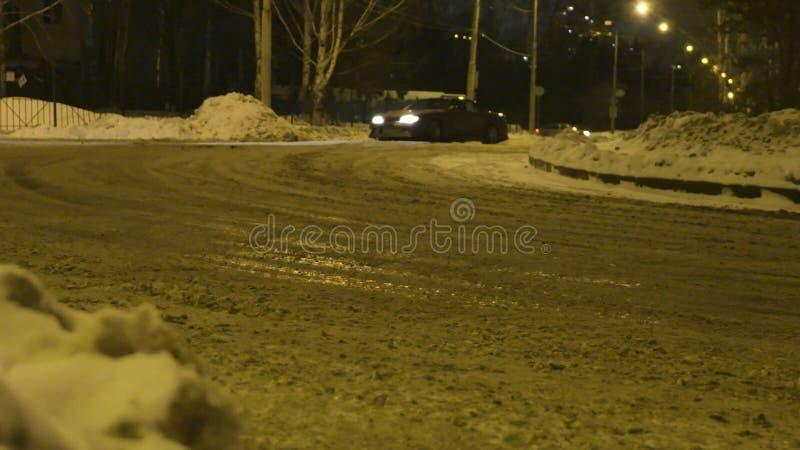 Autoafwijkingen op snow-covered weg in nachtstad actie Modieuze nieuwe autodraaien scherp op inschakelen snow-covered weg binnen royalty-vrije stock foto