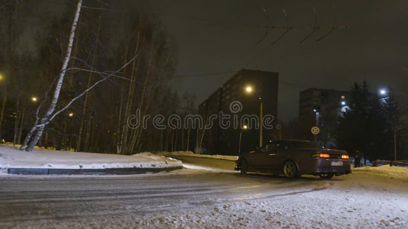 Autoafwijkingen op snow-covered weg in nachtstad actie Modieuze nieuwe autodraaien scherp op inschakelen snow-covered weg binnen stock foto