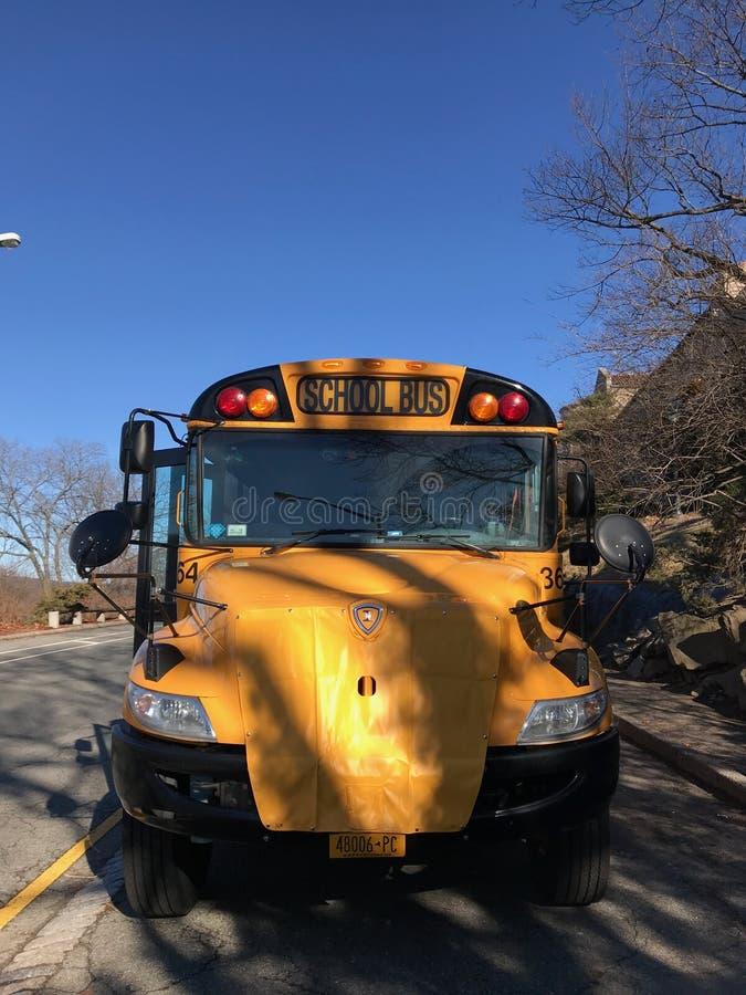 Autobús amarillo de la escuela en la calle en un día soleado contra el cielo azul y el camino imagen de archivo