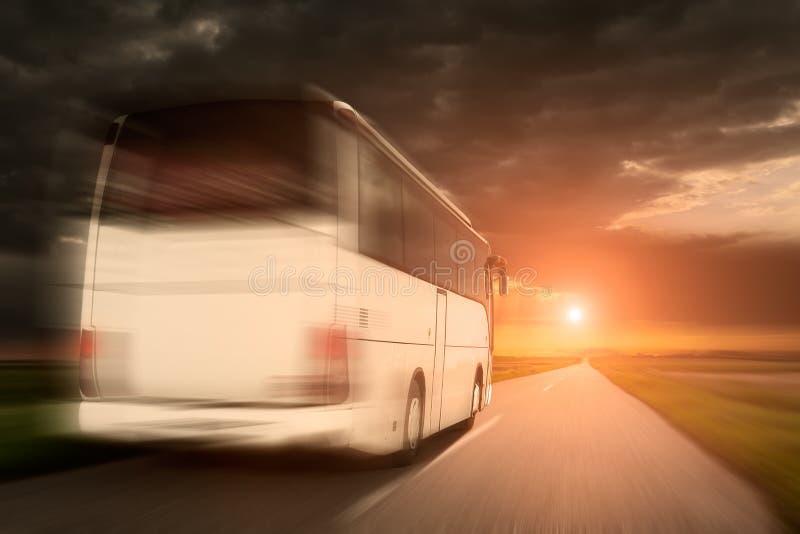 Autobús blanco en la velocidad que conduce en una carretera de asfalto vacía foto de archivo