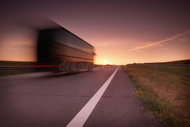Autobús borroso en la velocidad en la carretera en la puesta del sol imágenes de archivo libres de regalías