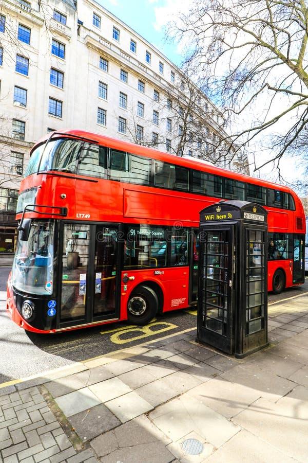 Autobús de Londres cerca de una cabina de teléfono del wifi imagenes de archivo