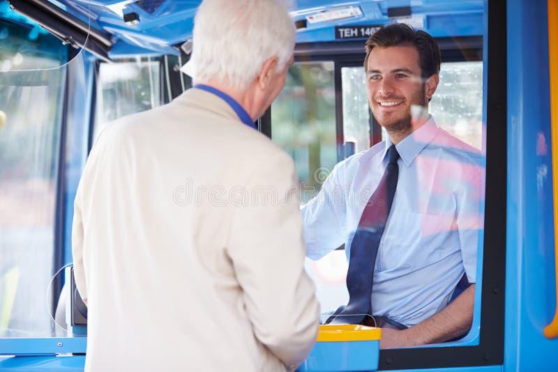 Autobús del embarque del hombre mayor y boleto de la compra fotografía de archivo