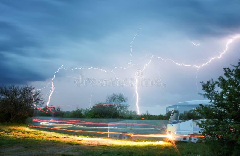 autobús en el campo que conduce contra el contexto de un cielo y de un relámpago tempestuosos imágenes de archivo libres de regalías