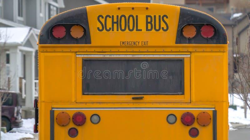 Autobús escolar amarillo del panorama claro con la ventana rectangular y varias luces de señal en la parte posterior imagen de archivo