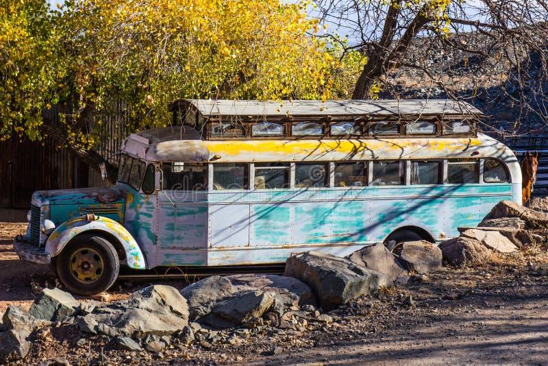 Autobús escolar convertido abandonado viejo en yarda del salvamento imagen de archivo libre de regalías