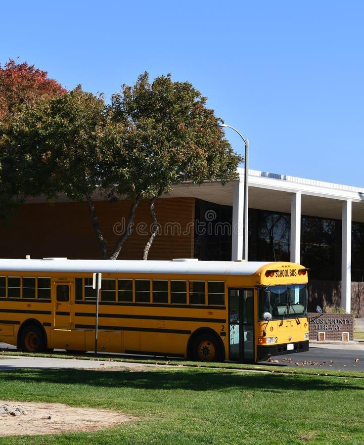 Autobús escolar parqueado mientras que los niños visitan una biblioteca local fotos de archivo libres de regalías
