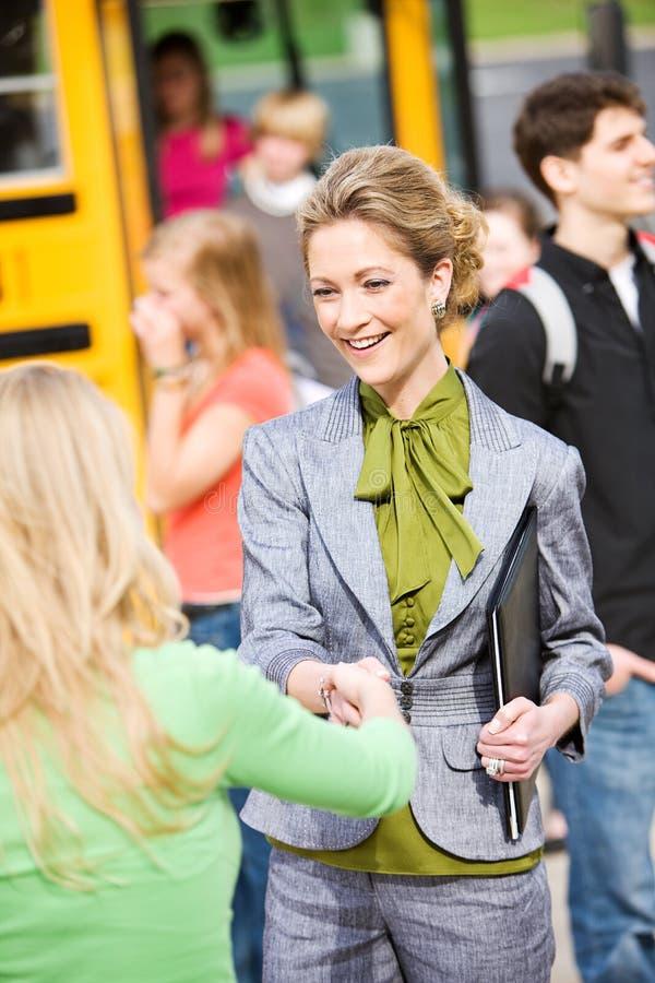 Autobús escolar: Profesor Welcomes Student a enseñar foto de archivo libre de regalías