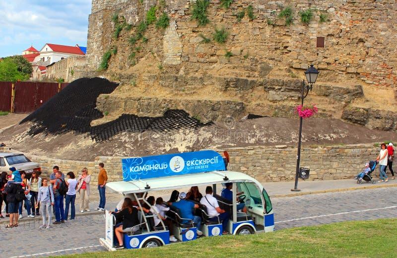 Autobús turístico en movimiento cerca de la pared del castillo de Kamianets-Podilskyi imagen de archivo libre de regalías