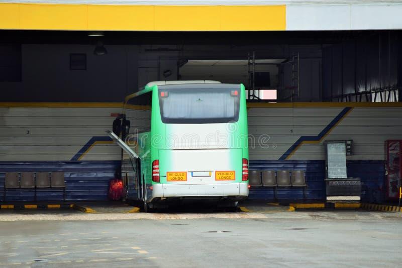 Autobús verde y blanco en un término de autobuses abierto fotos de archivo