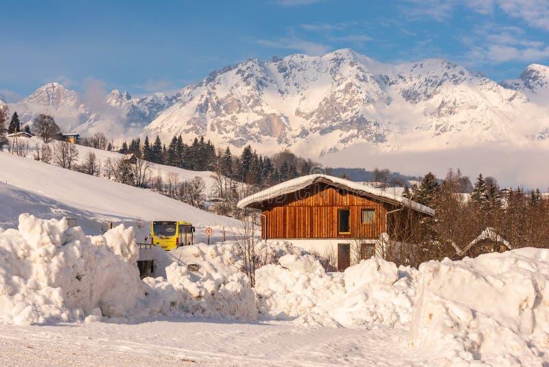 Autob?s austr?aco y casa de madera Monta?as en el fondo Región Schladming-Dachstein, Liezen, Estiria, Austria del esquí fotos de archivo libres de regalías
