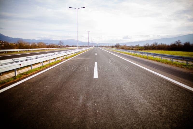 Autobahn auf szenischen grünen Wiesen einer sonniger Tagesabflussrinne Reisende Langstrecke der Autobahn Asphaltlandstraßenstraße stockbild