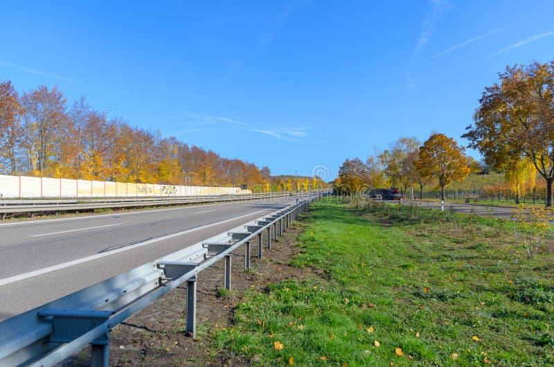 Autobahn mit Leitplanke im Herbst stockfotos