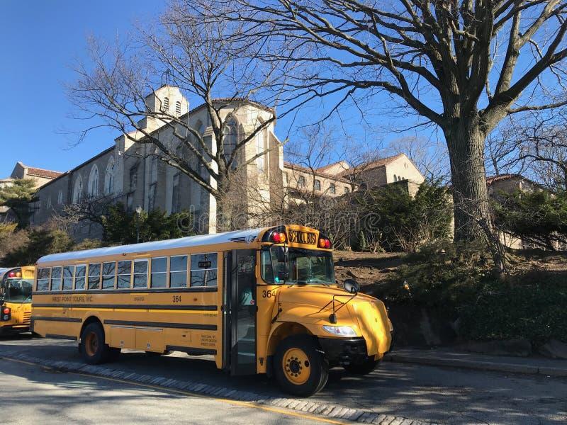 Autobus jaune d'école sur la rue un jour ensoleillé contre le ciel bleu et la route image stock