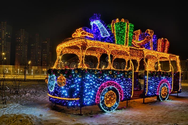 Autobus lumineux de nouvelle année avec des cadeaux la nuit photos stock
