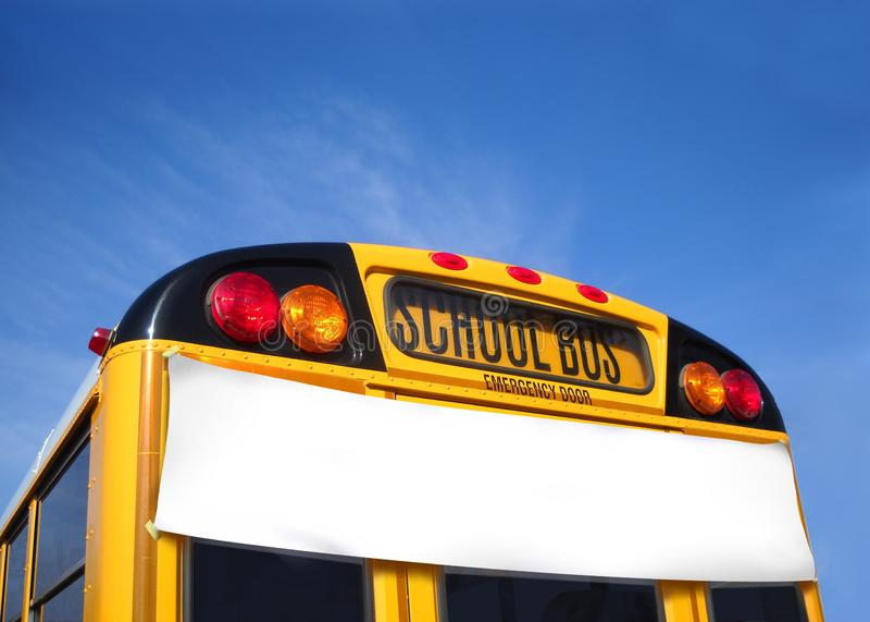 Autobus scolaire avec la bannière blanche - blanc pour ajouter le texte - sous le ciel bleu photo libre de droits
