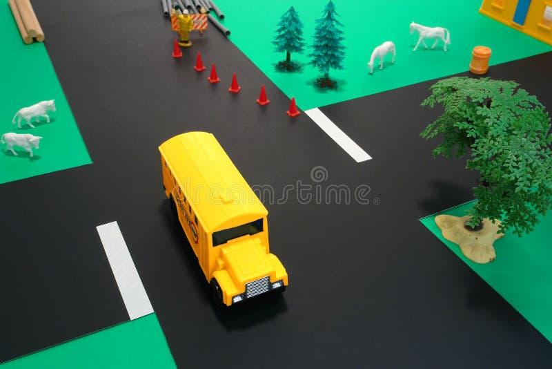 Autobus scolaire de jouet d'éducation de gestionnaire sur la route dangereuse photo stock