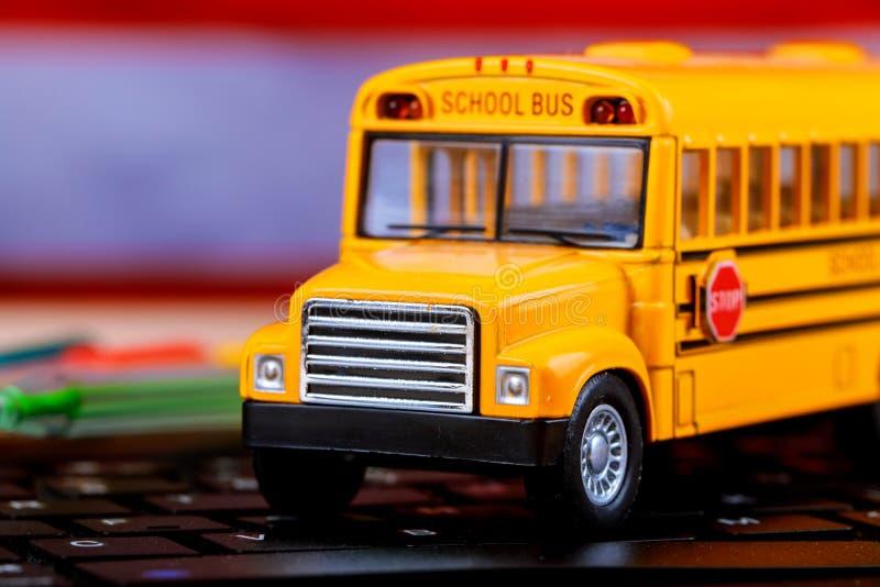 Autobus scolaire jaune sortant d'un écran d'ordinateur illustrant l'ordinateur en ligne de clavier d'éducation image stock
